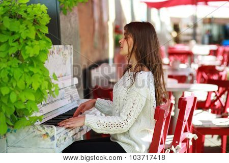 Girl Playing On An Old Piano In Street Cafe