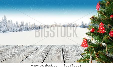 Winter background with Christmas tree and blur landscape. Empty wooden planks on foreground. Copyspace for text