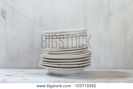 stack of white plates on wooden white table