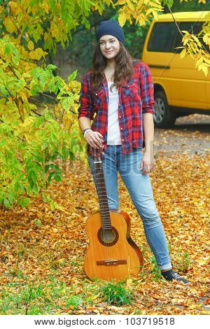 Full Length Portrait Of Young Guitar Player Woman At Yellow Minibus And Autumn Yellow Fallen Leaves