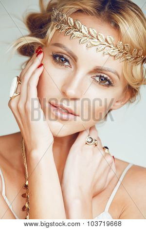young blond woman dressed like ancient greek godess, gold jewelry close up
