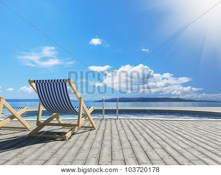 Swimming pool with deckchairs and beautiful view of sea