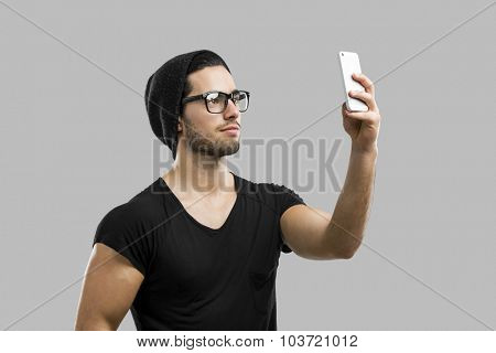 Portrait of handsome young man making a selfie, isolated over a gray background