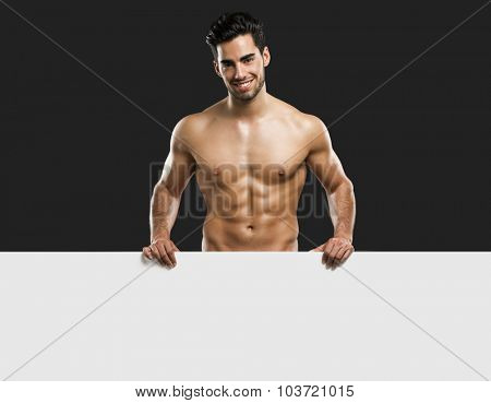Handsome and sexy young man holding a cardboard, isolated over gray background