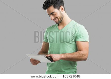 Handsome young man working with a tablet, isolated over gray background