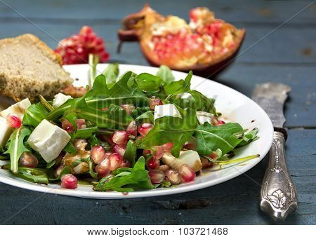 Rocket Salad With  Feta Cheese And Pomegranate On An Rustic Wooden Table