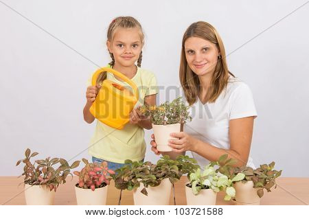 Mom And Daughter Take Care Of Potted Flowers