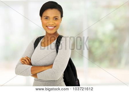 portrait of pretty female african college student with arms crossed
