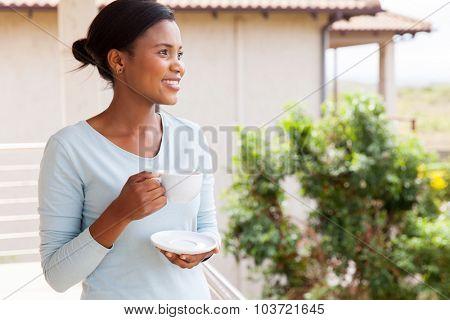 pretty african american woman drinking coffee on balcony
