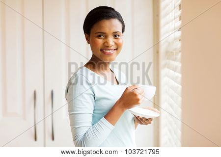 happy afro american woman drinking tea at home