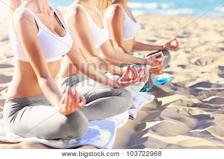 A midsection of a group of women practising yoga on the beach