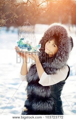 Young woman and birds in a cage in the winter forest Winter woman on background of winter landscape sun. Fashion girl in forest wonderland. Winter sunset scene. Model in sunlight, backlight