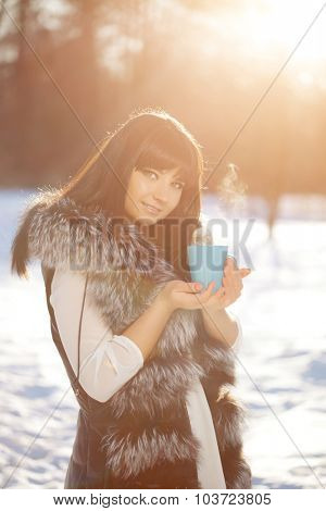 Young woman with a cup of hot drink in winter wood Winter woman on background of winter landscape sun. Fashion girl in forest wonderland. Winter sunset scene. Model in sunlight, backlight