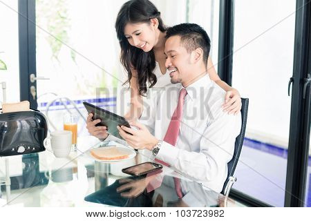 Asian couple having breakfast before man goes to office, he is checking the emails or news with his wife