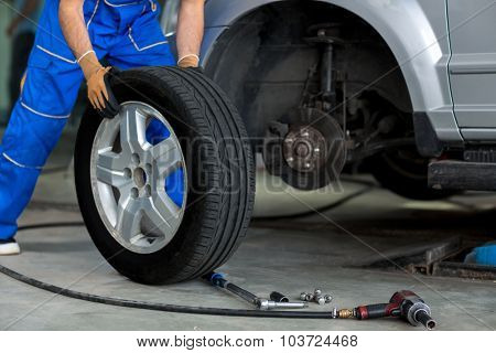 mechanic changing a wheel of a modern car  in a workshop