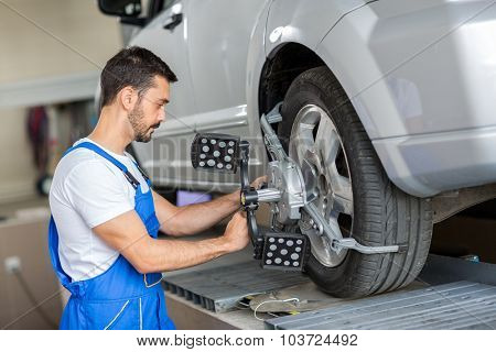 car mechanic installing sensor  adjustment and automobile wheel