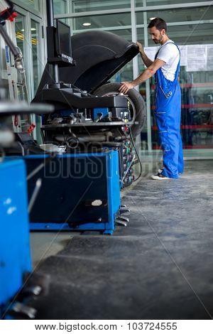 mechanic balancing  car wheel on balancer