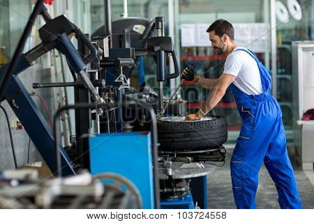 repairman balancing  car wheel on balancer in workshop