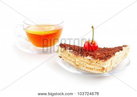 cherry cake and golden tea on white