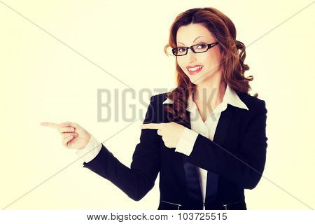 Beautiful businesswoman in eyeglasses pointing to the left.