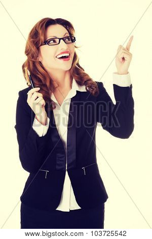 Beautiful businesswoman in eyeglasses pointing up.