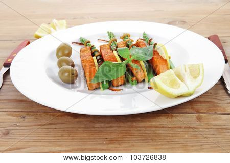 roasted salmon slices with asparagus lemon fried orange peel green olives and cutlery on white plate over wooden table