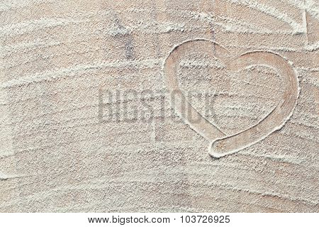 heart made from white flour on kitchen table