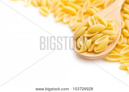 uncooked italian pasta in wooden spoon on white background
