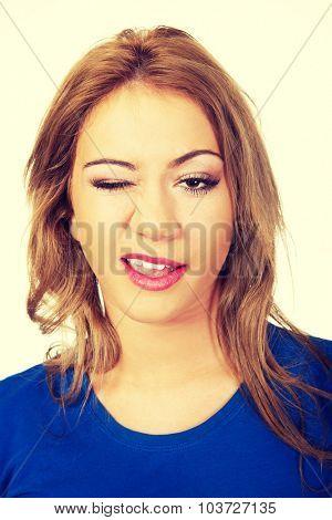Beautiful happy woman blinks her eye.