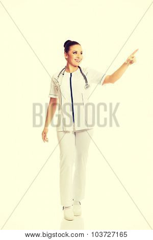 Full length female doctor pointing to the right.