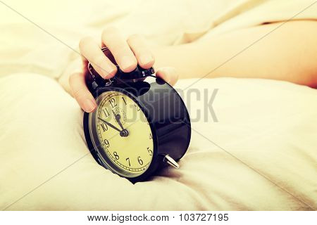 Exhausted man being awakened by an alarm clock in his bedroom.