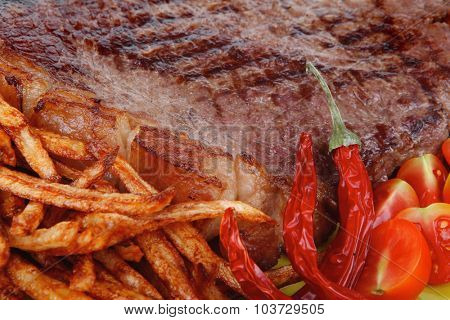 main course : grill beef steak with potato chips and fresh cherry tomato , dry red hot chili peppers on green plate isolated on white background