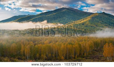 sunrise in autumn taiga and mountains