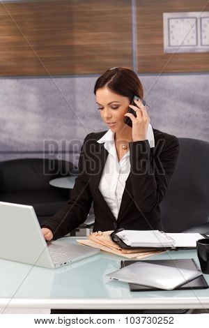 Businesswoman sitting at desk, working with laptop computer, talking on mobilephone.