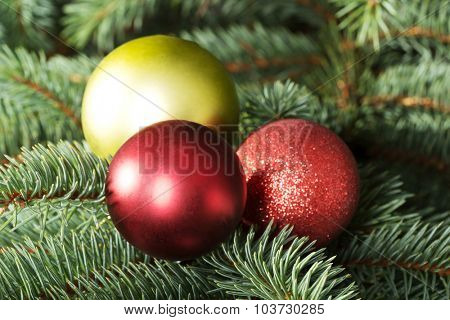 Three christmas balls hanging on a twig.On green background.