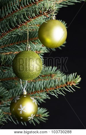 Three christmas balls hanging on a twig. Over black background.
