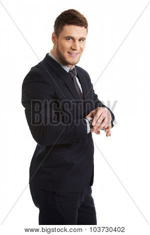 Handsome businessman checking time on his wrist watch.