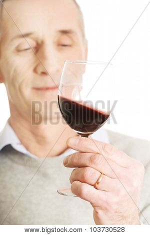 Handsome mature man tasting red wine.