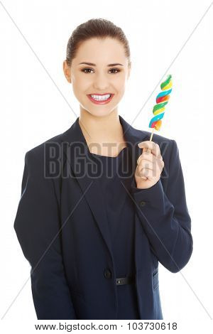 Young happy businesswoman holding spiral lolipop