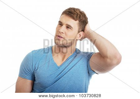 Young handsome pensive man with hand behind head.