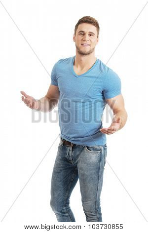 Handsome young man shrugging his hands.