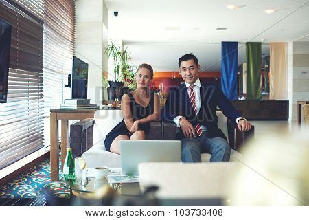Young woman and men entrepreneurs dressed in elegant clothes resting after conference