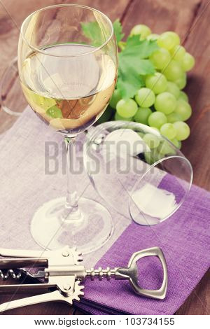 White wine glass and grapes on wooden table. Toned