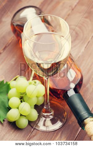 White wine and grapes on wooden table. Toned