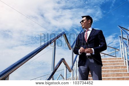Portrait of young successful director standing with a cigarette against blue sky with copy space