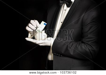Elegant Man In Tuxedo Holding Piggy Bank And Banknote