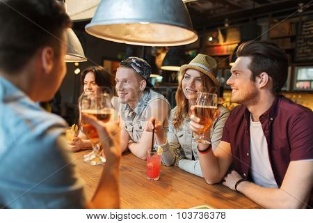 people, leisure, friendship and communication concept - group of happy smiling friends drinking beer and cocktails talking at bar or pub