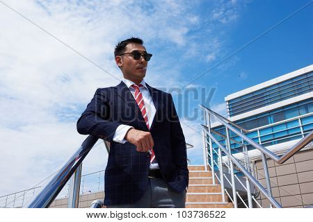 Confident managing director in formal wear relaxing outdoors in sunny summer day