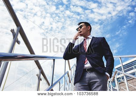 View from below of young confident businessmen smoking cigarette while standing outside office
