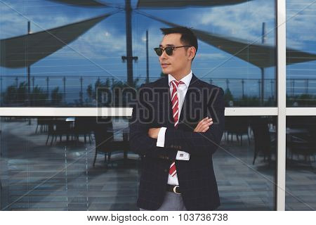 Portrait of young confident managing director with arms crossed standing near modern office building